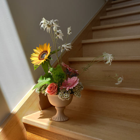 Sitting on a stair on a staircase is a light pink vase with an intricate stem. Bright coloured flowers are arranged in the vase, a yellow sunflower, green fluffy flowers, pink roses. Sunlight is shining in on the vase from a window out of the photo.