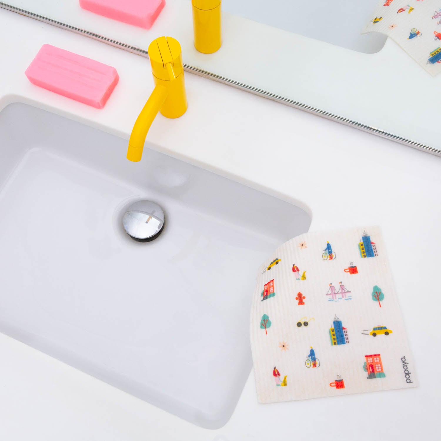 Reusable paper towel with city pattern design hanging over a white sink with a yellow faucet and pink bar of soap