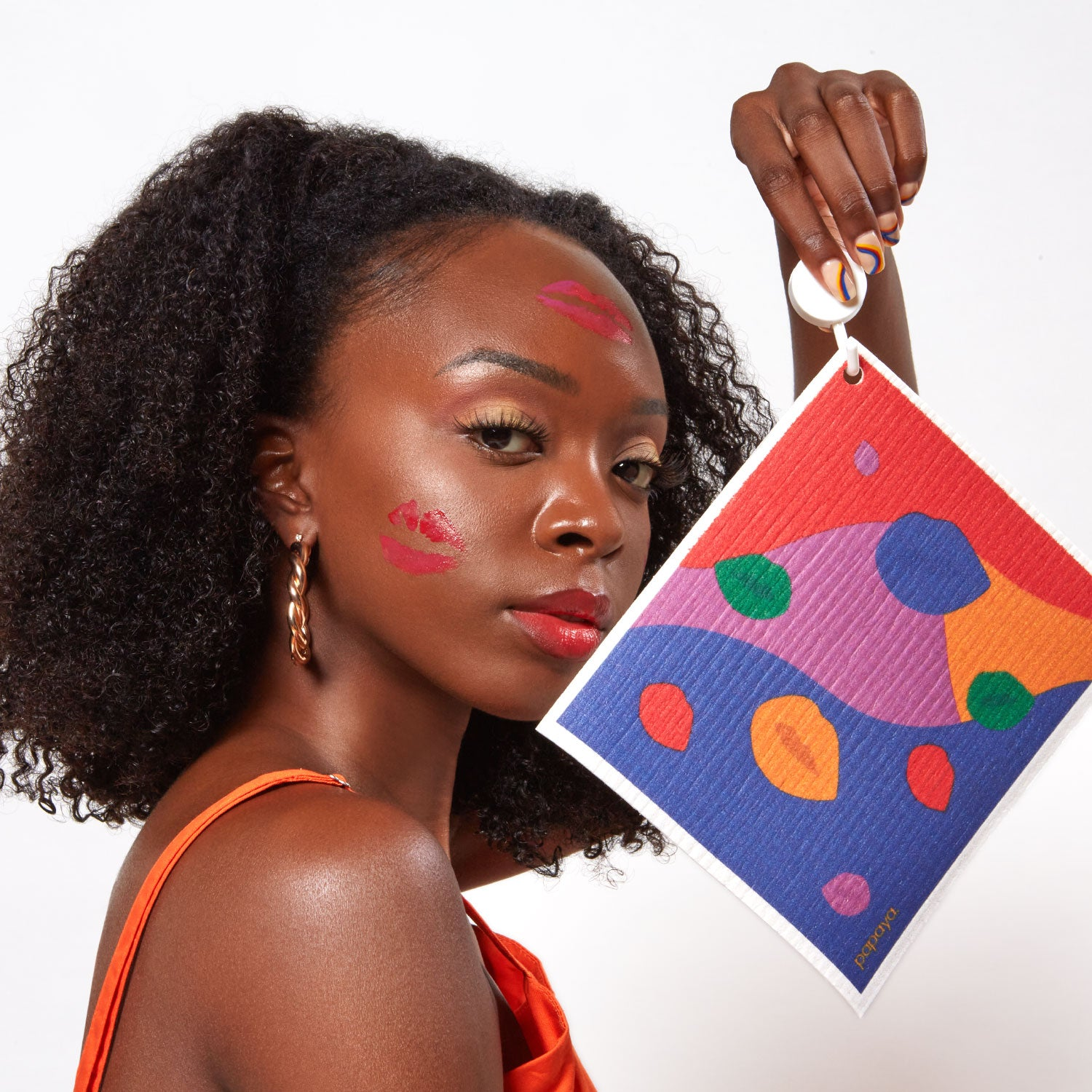 Model holding reusable paper towel with bright lips design and lipstick kisses on her face