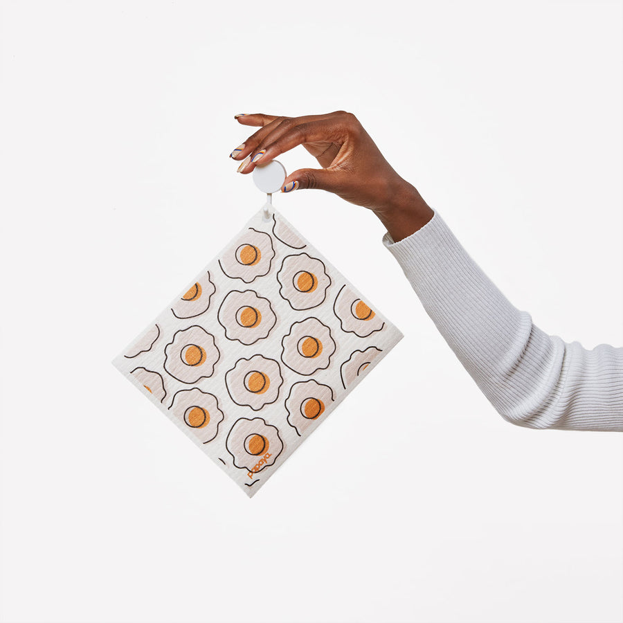 Model holding a hook with a reusable paper towel hanging on it with a cute egg design