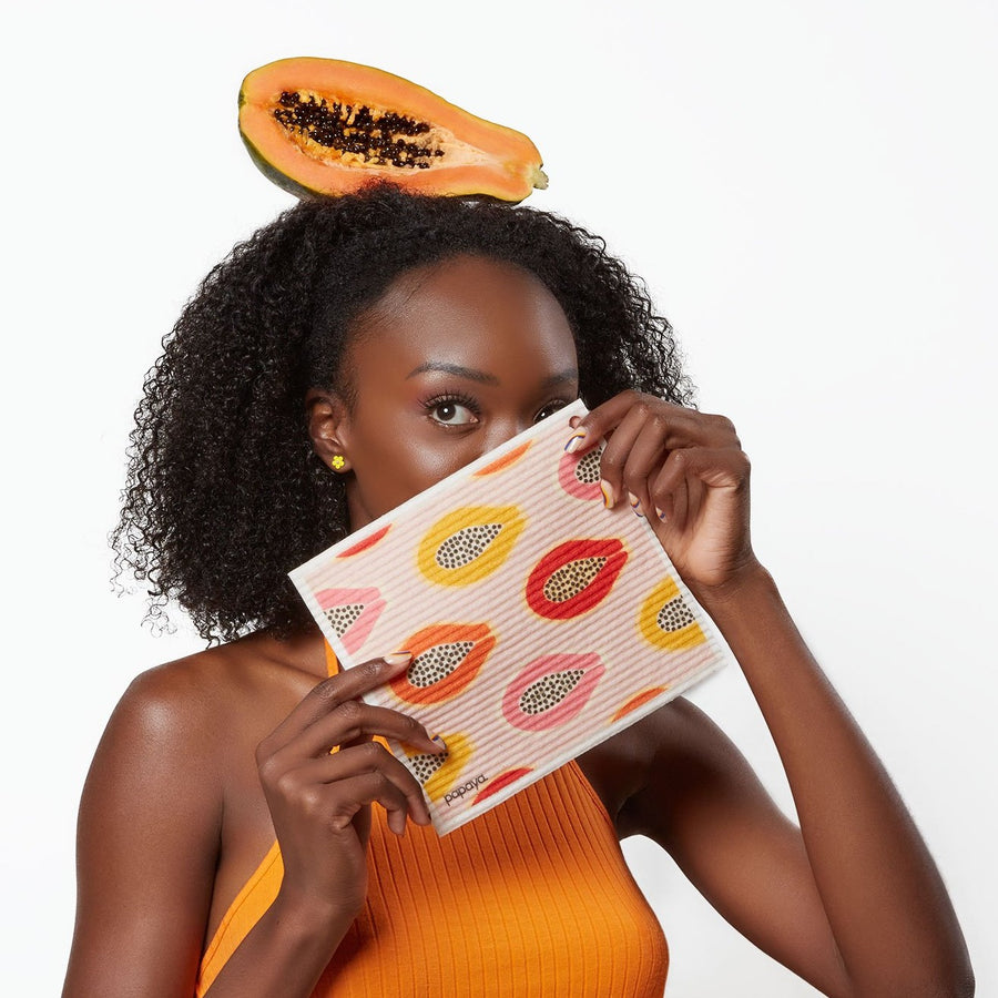 Model holding reusable paper towel with pink yellow and orange papayas design and a papaya on her head