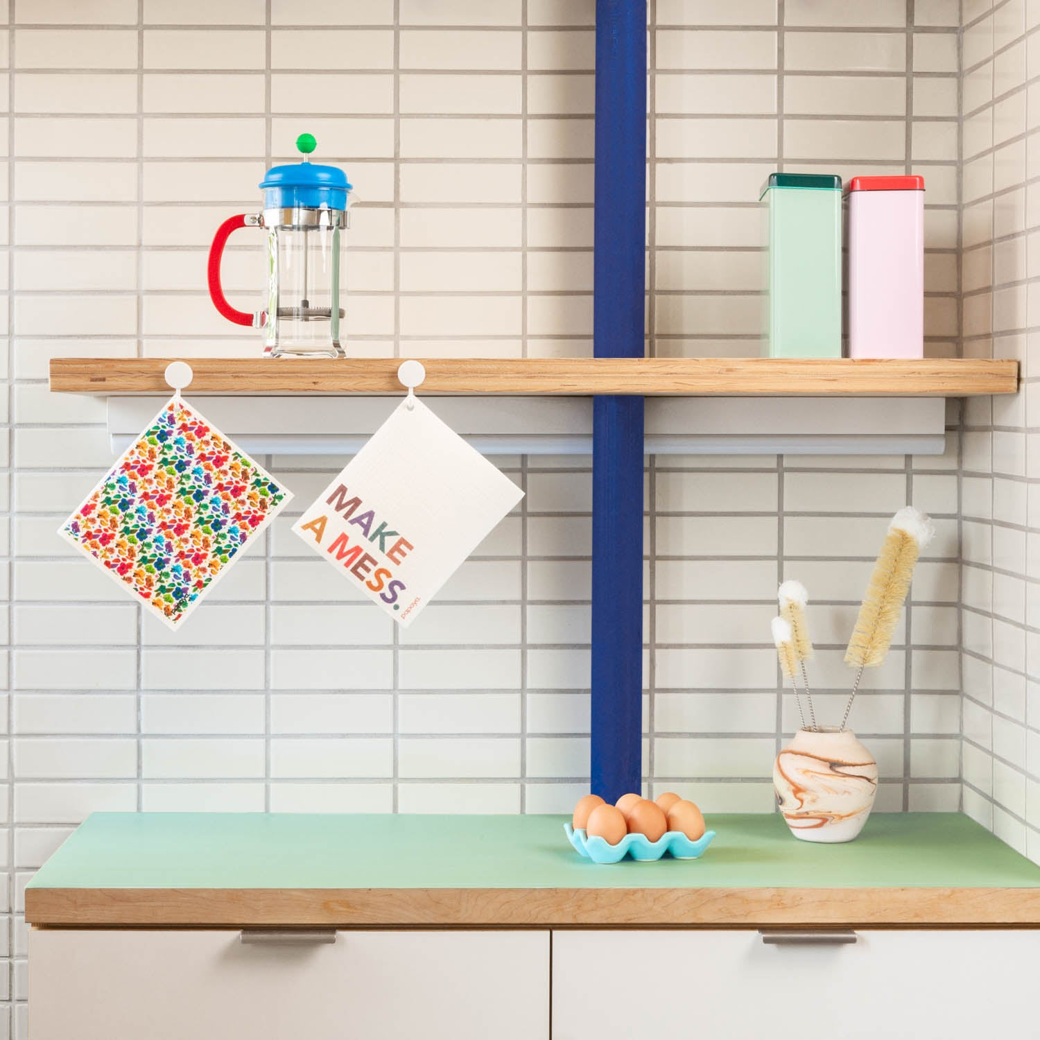 Two reusable paper towels hanging on hooks in modern kitchen with colorful floral design and make a mess words
