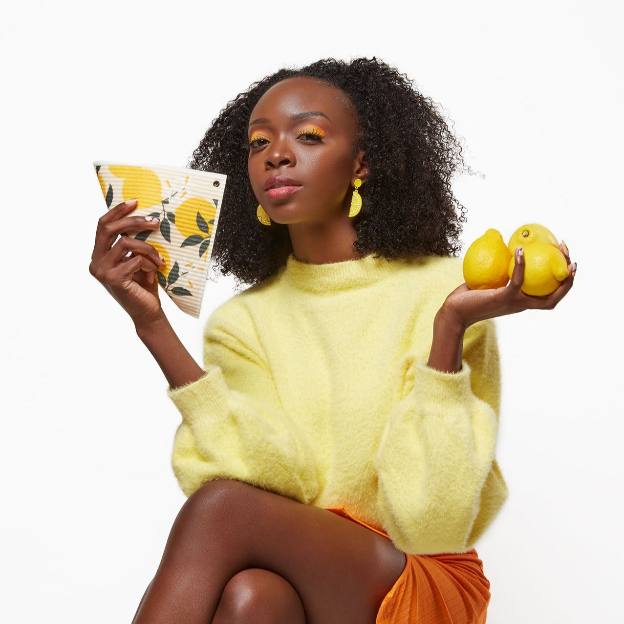 Model holding reusable paper towel with lemon design in one hand and three lemons in the other