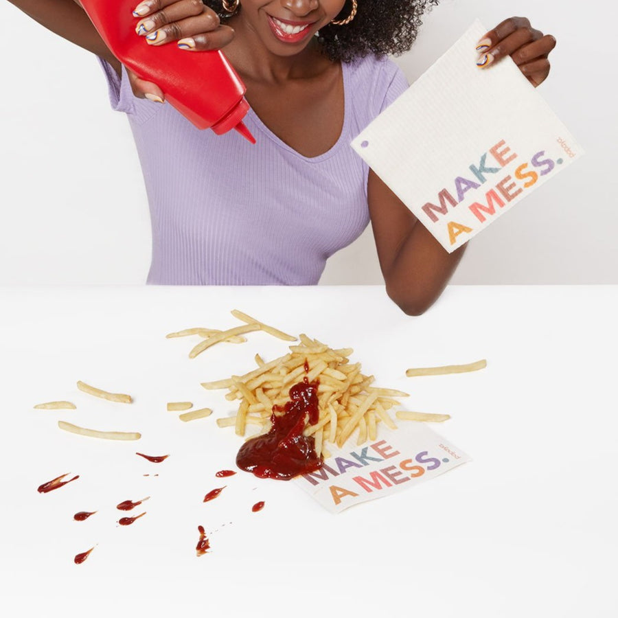 Reusable paper towel that says Make A Mess on a table covered in french fries and ketchup
