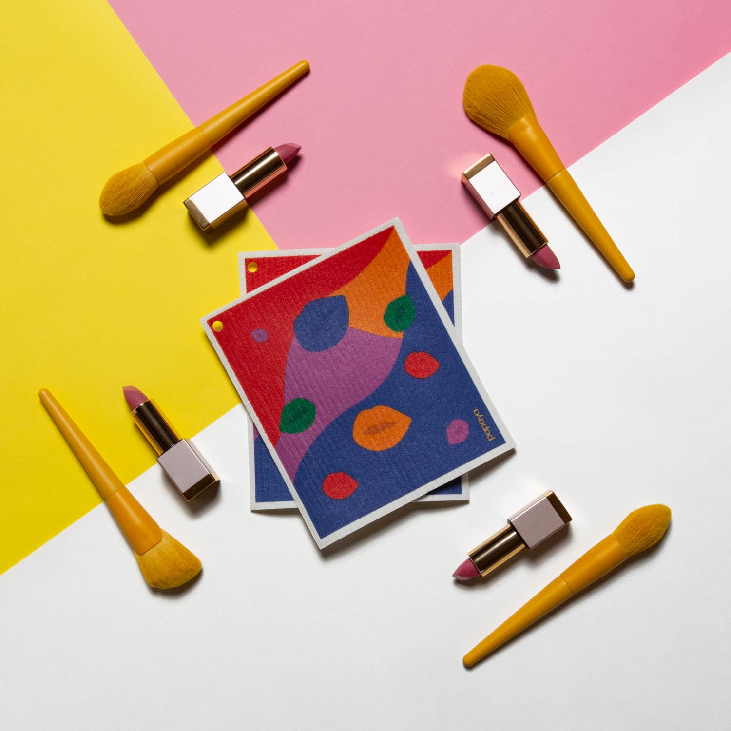 Two reusable paper towels in a colorful lip design surrounded by yellow makeup brushes and lipsticks