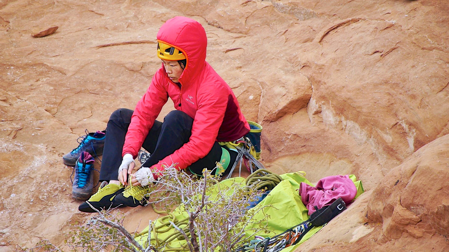 Rock climber woman tightening her shoes