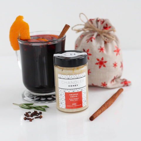 Orange Grove Chandler Honey raw Canadian honey with a glass of mulled wine, garnished with an orange zest and cinnamon stick