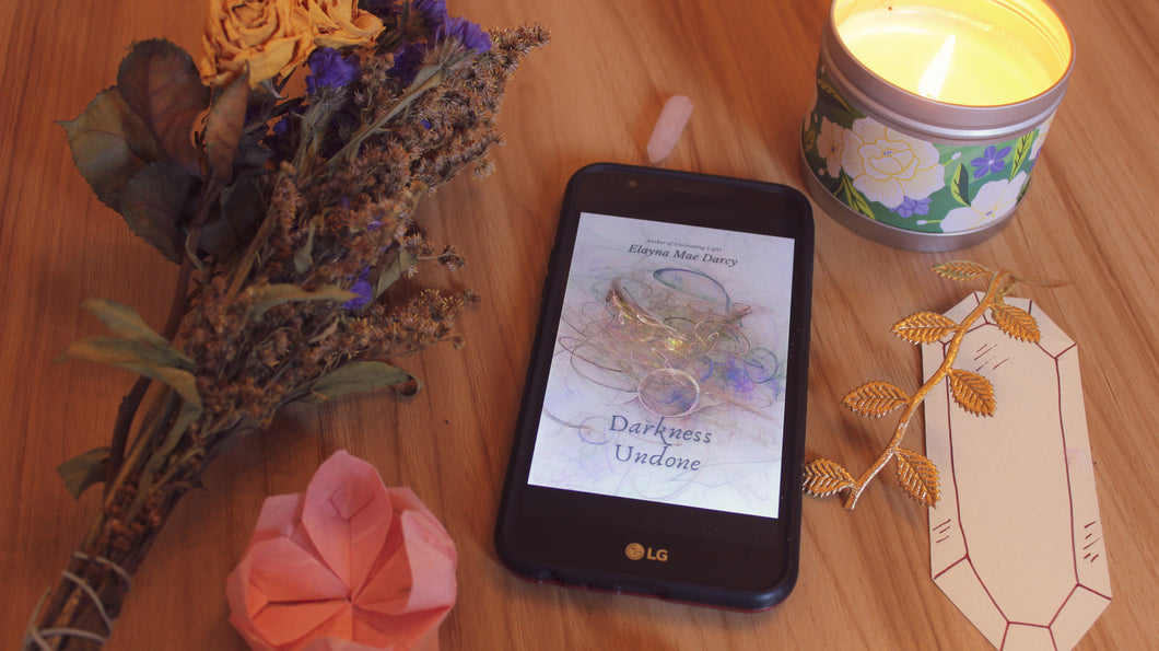 Phone featuring the PDF ebook cover of DARKNESS UNDONE, surrounded by a crystal, dried flowers, a candle, and a bookmark.