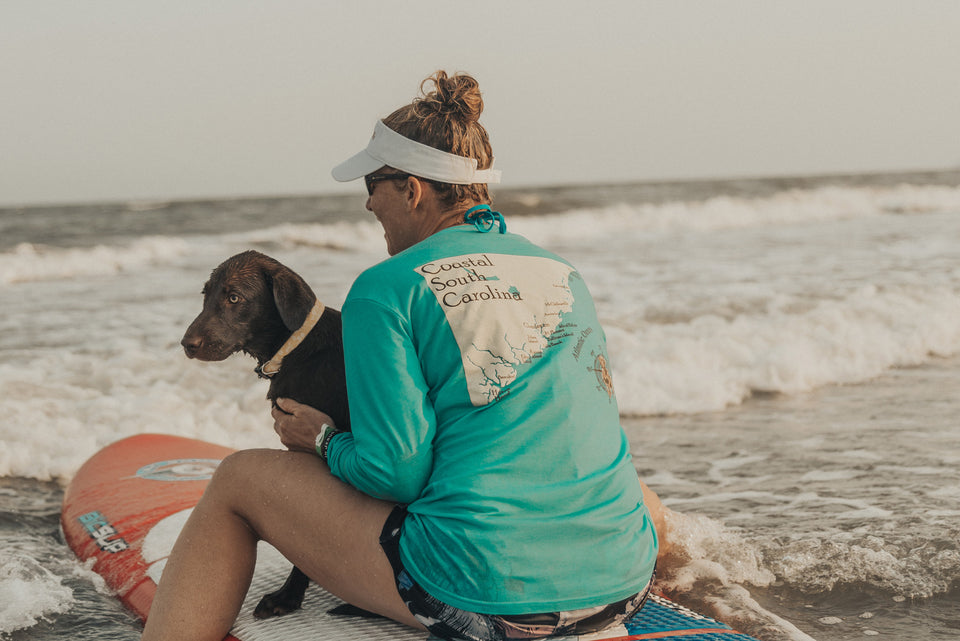 Puppy and girl sitting on a paddleboard local dog charleston
