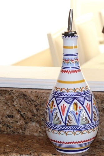 A hand painted olive oil dispenser from Spain.  White background with patterns in shades of blues/golds/red/soft green and browns.