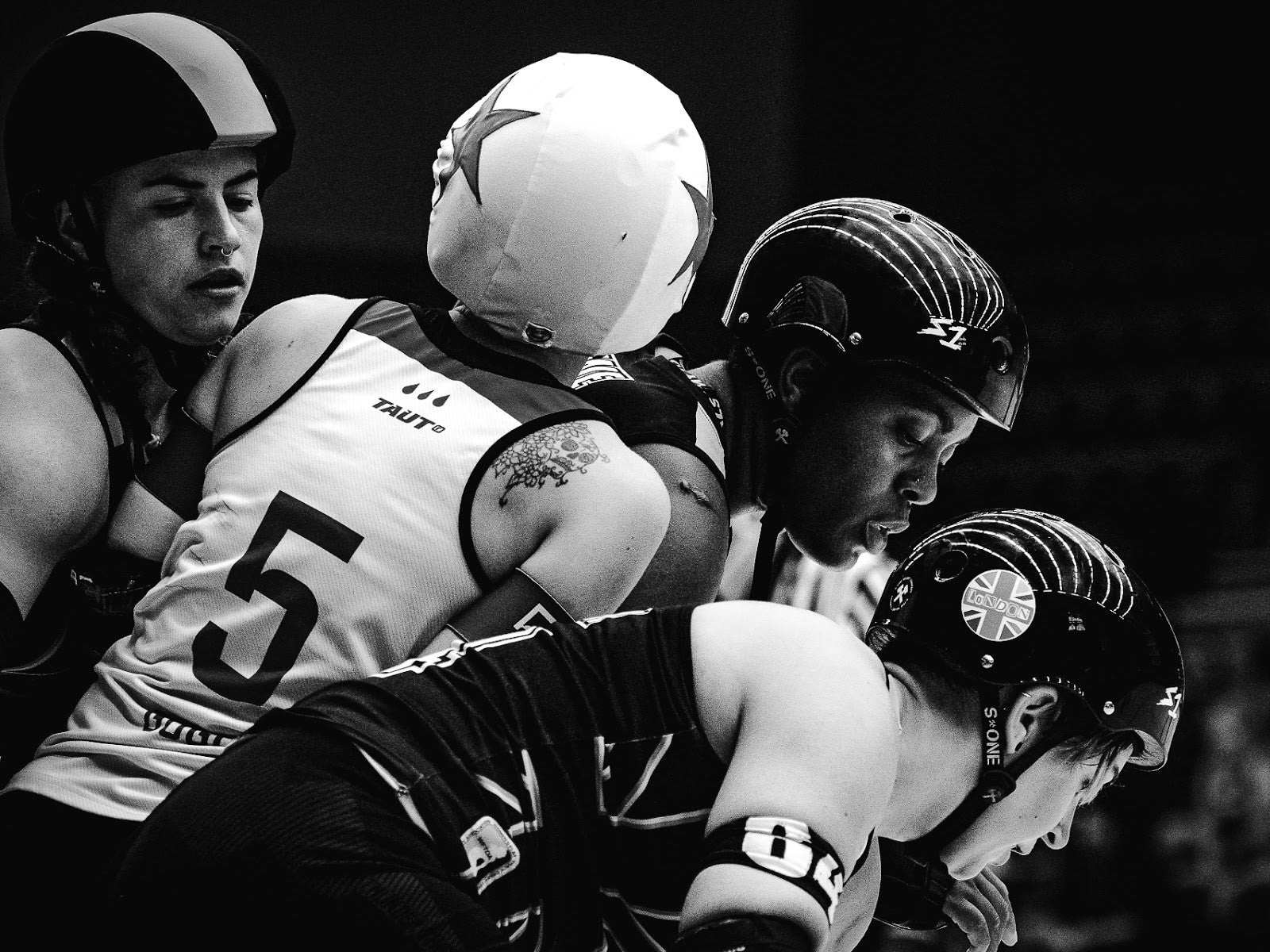 The beauty of great composition: Swaffield, jammer for Rainy City Roller Derby caught in a London Roller Derby 3-wall and pushing to escape. A moment that radiates calmness and shows the extreme concentration on the faces of the blockers with a framing indicating the direction of the game. London Roller Derby vs Rainy City Roller Derby at WFTDA Playoffs in Malmö (Sweden), 2017. ©Anja Wettergren