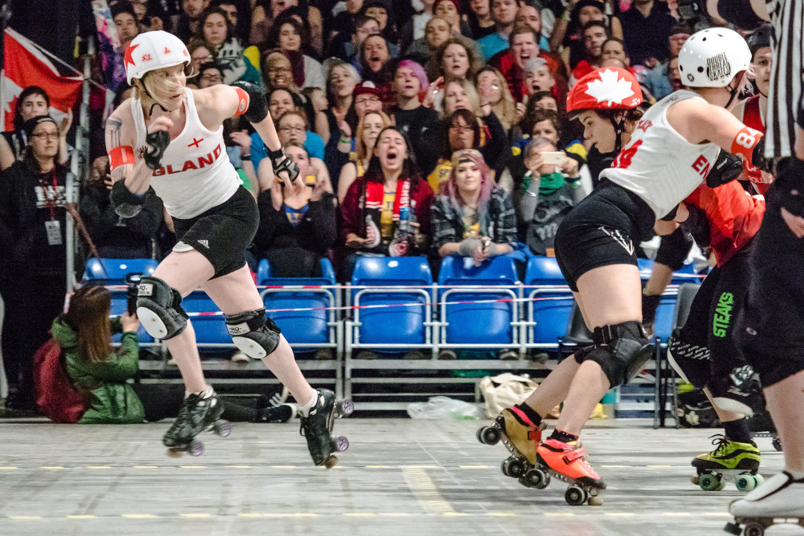 A moment in time composed to tell a story that went down during the Women's Roller Derby World Cup in 2018. Team England vs Team Canada: the English jammer Alex Wilde exits the pack running, while Canadian jammer and STEAKS® CRW alumni Falcon Punch is still stuck in the English wall, held – by what seems to be – the last blocker. Alex has her eye on the pack: to check if she is being hunted down or to check to see where Falcon is? That part of the story remains untold. ©Anja Wettergren