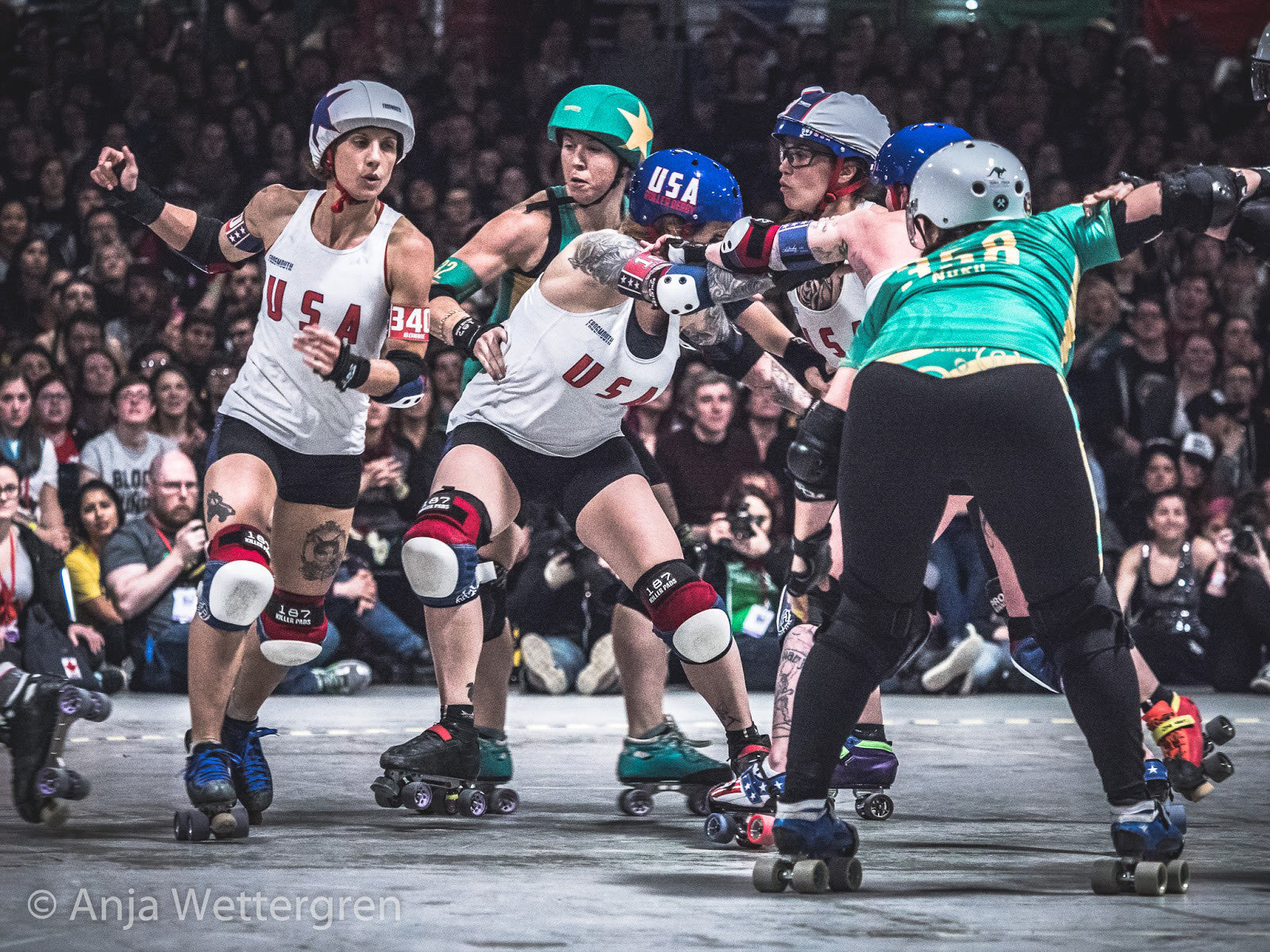 An older edit from Anja with high contrast, grittiness & drama added through high gradation. If you take a closer look at Australia's jammer Jambi's upper arm you can almost feel the power, strength and concentrated movement caught in the image. Team USA vs. Team Australia during the Roller Derby World Cup 2018 in Manchester, UK. ©Anja Wettergren