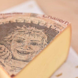 Large wheel of alpine cheese with a picture of a face on the label