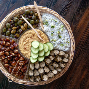 Platter with dolmas, hummus, tzatziki, olives, and almond stuffed dates