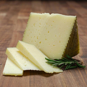 Wedge of firm cheese with green rind