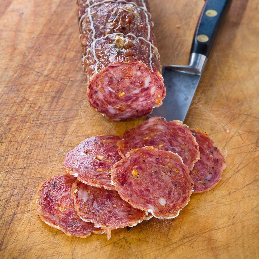 Slices of salami with orange zest and red pepper
