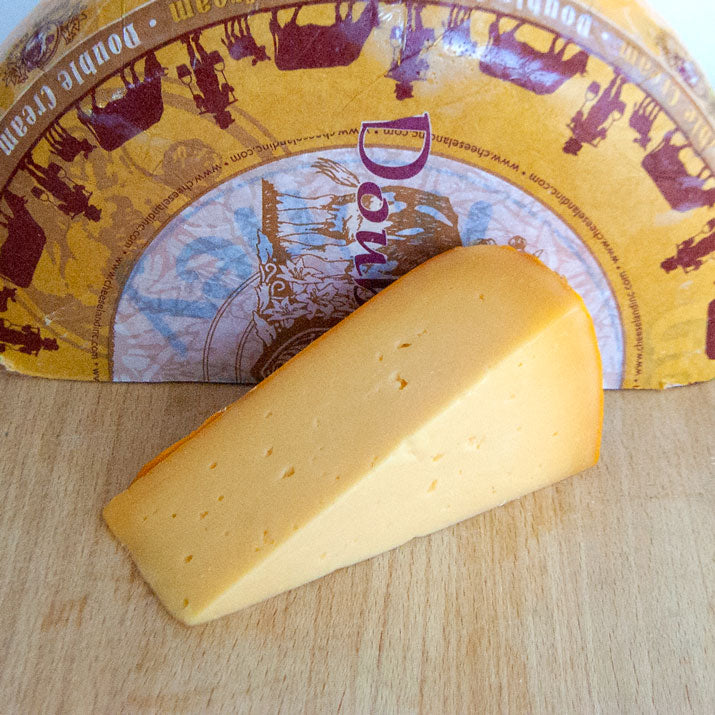 wedge of yellow semi firm gouda cheese