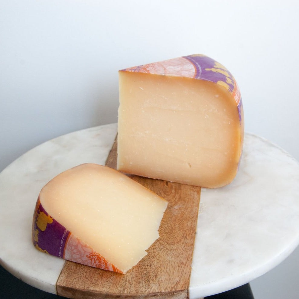 Two wedges of light orange sheep's milk gouda