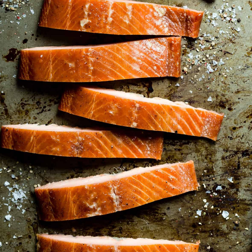 several pieces of hot smoked salmon on a baking pan with flaky salt