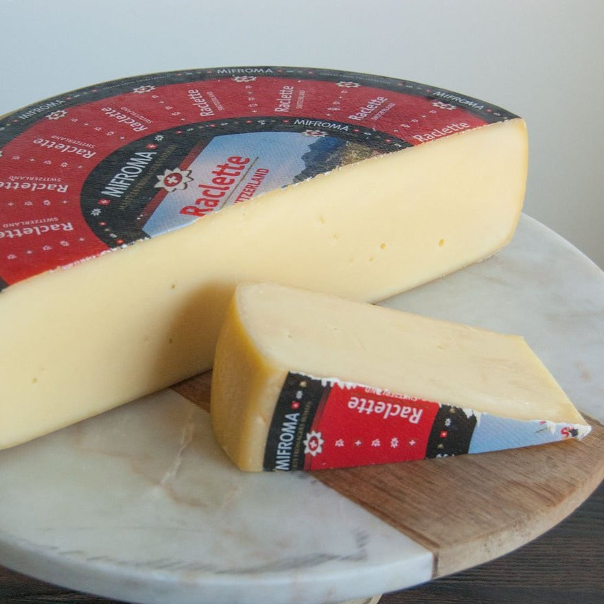 Half wheel of firm yellow raclette cheese