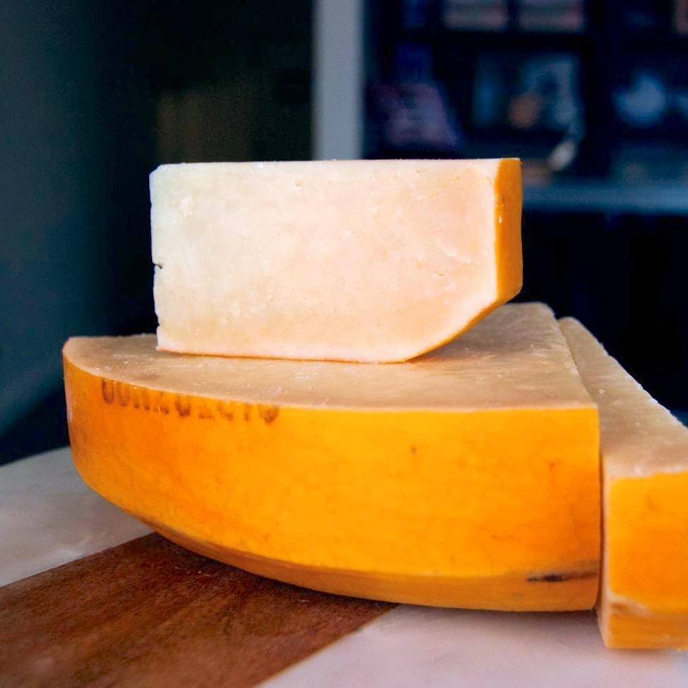 wedge of firm yellow cheese with a gold rind