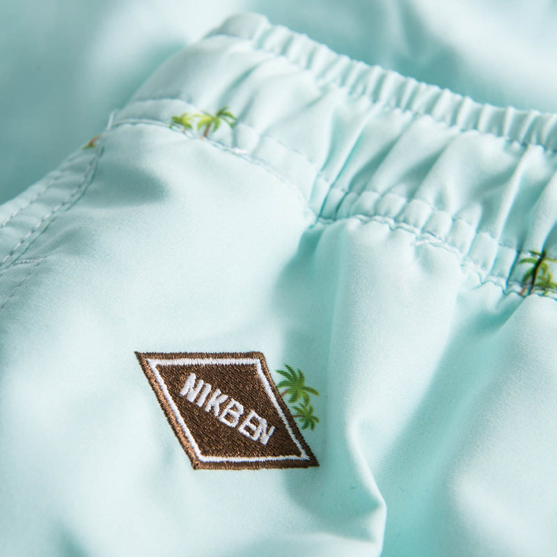 Logo on turquoise printed swim trunks