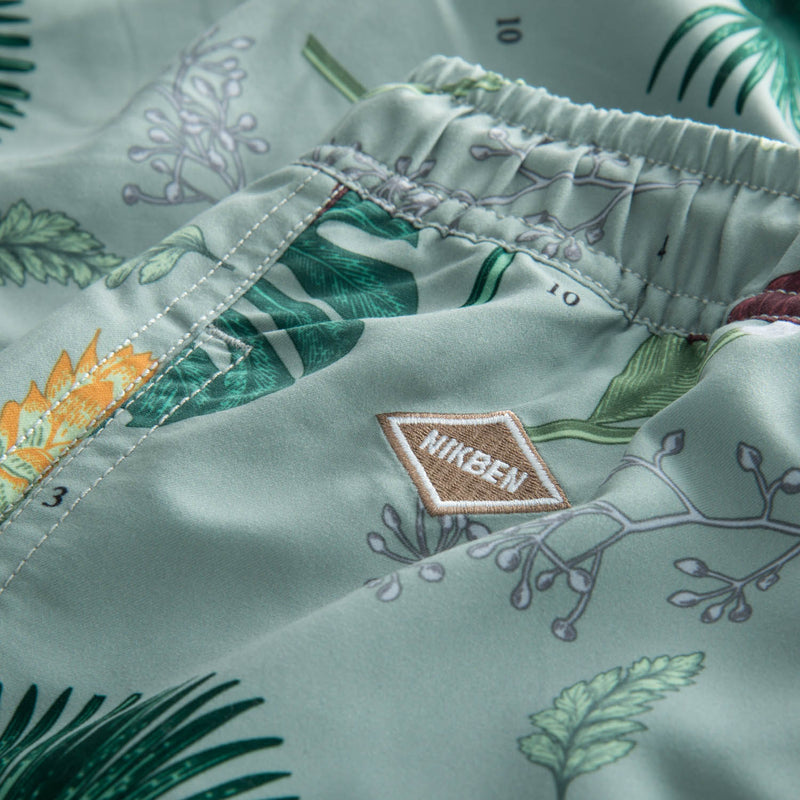 Logo on green flower printed swim trunks