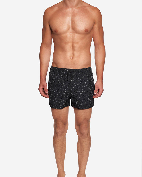 Model wearing black mid length swim trunks with white text