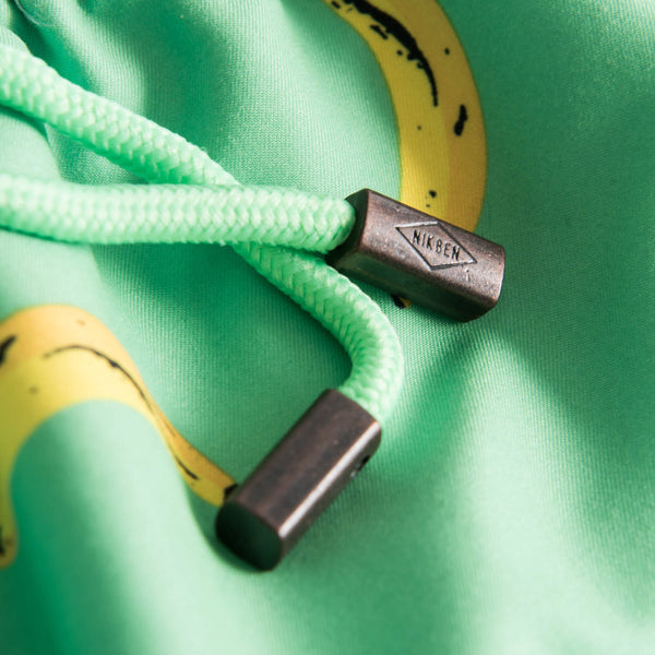 Drawstring waistband on green swim trunks with yellow bananas