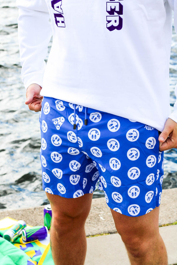 Model wearing blue swim trunks with white smiley print