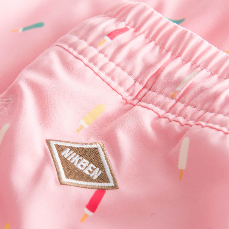 Brown logo on pink swim trunks with popsicle print