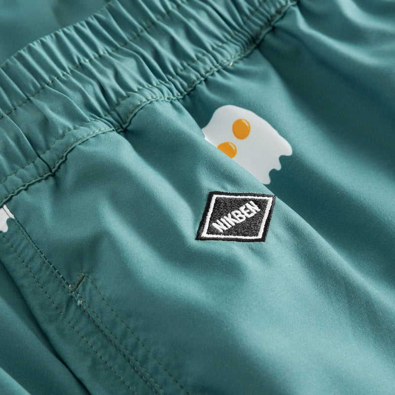 Logo on green swim trunks with egg print