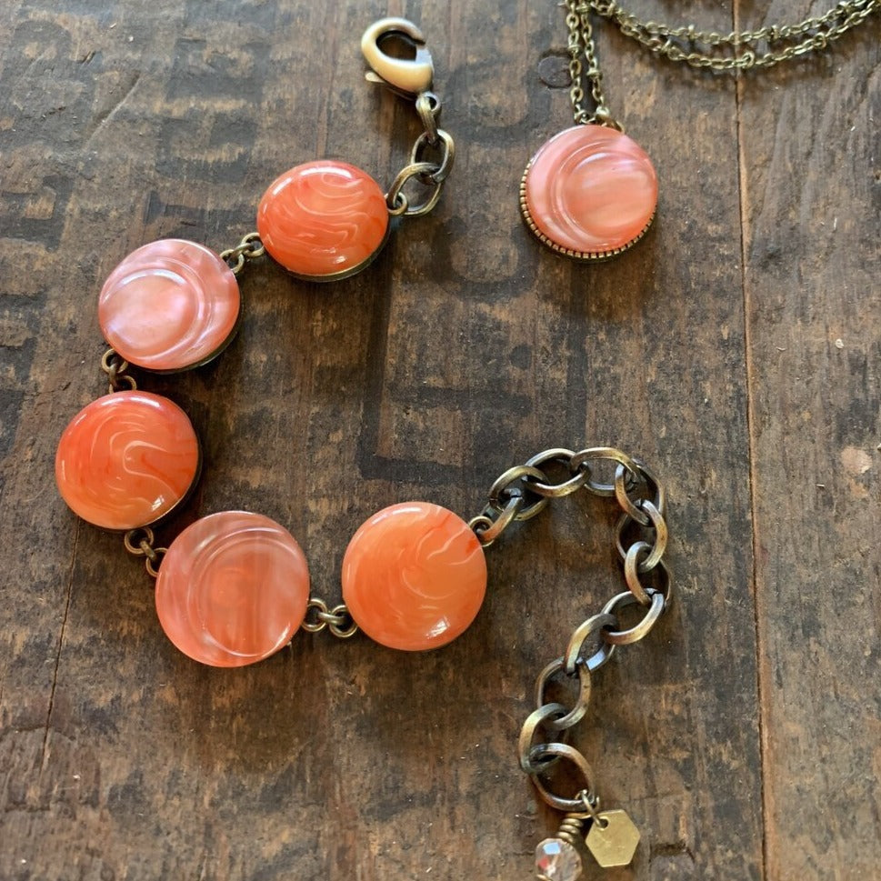 "Two beautiful unique pieces using colourful coral buttons from the 50s  The 5 buttons linked bracelet has two different shades of tangerine and coral and measures 10"" (connector gives extra length).  The necklace is on a delicate bronze ball chain and is 30 inches in length with a pretty coral pendant."
