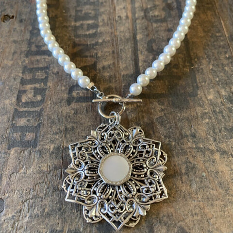 Late 1800s pearl button set in vintage silver filigree.  This pretty pendant hangs from a strand of pearlized agate and has a decorative toggle closure.