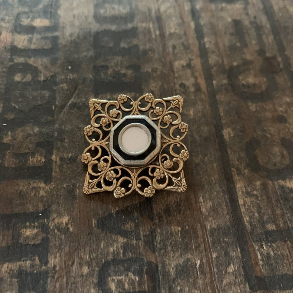 A ittle vest button from the late 1800s is the focal point for this brooch.