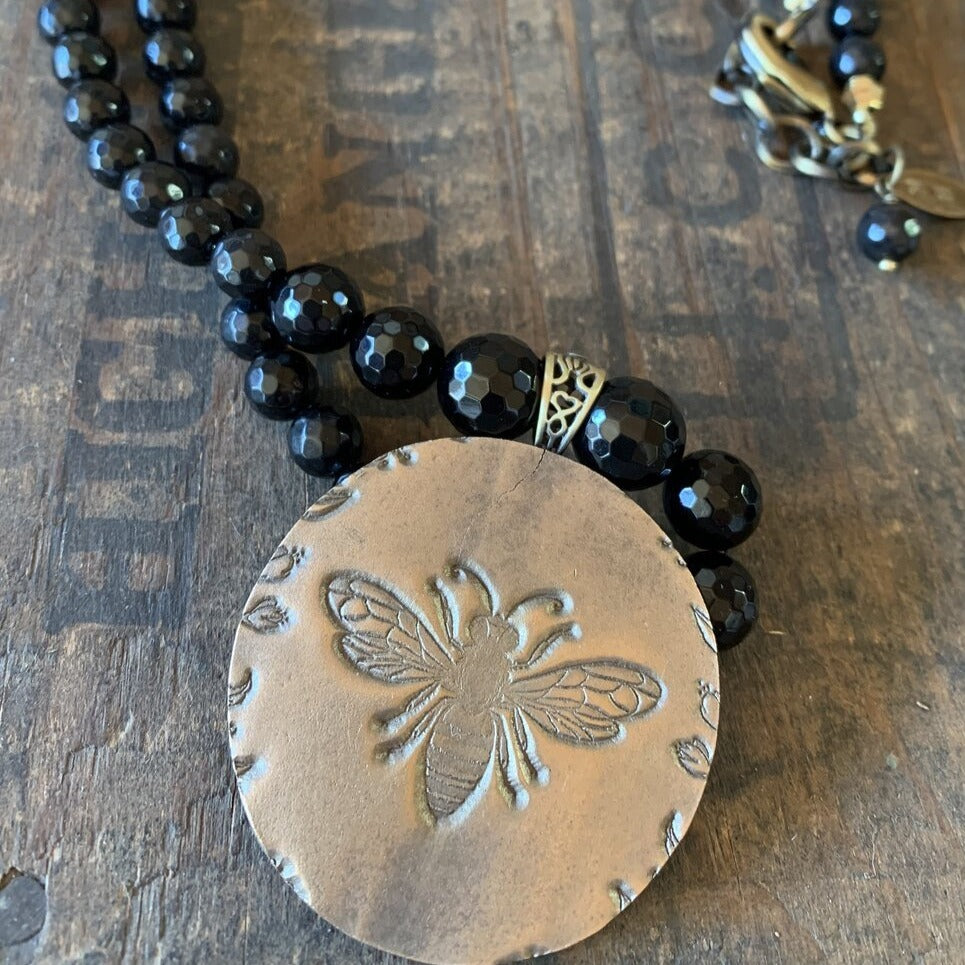 "An extra large, bronze pendant is created from an old button mold. It is strung on a strand of onyx and hangs roughly 26"" with a connector that can bring it to 28""."