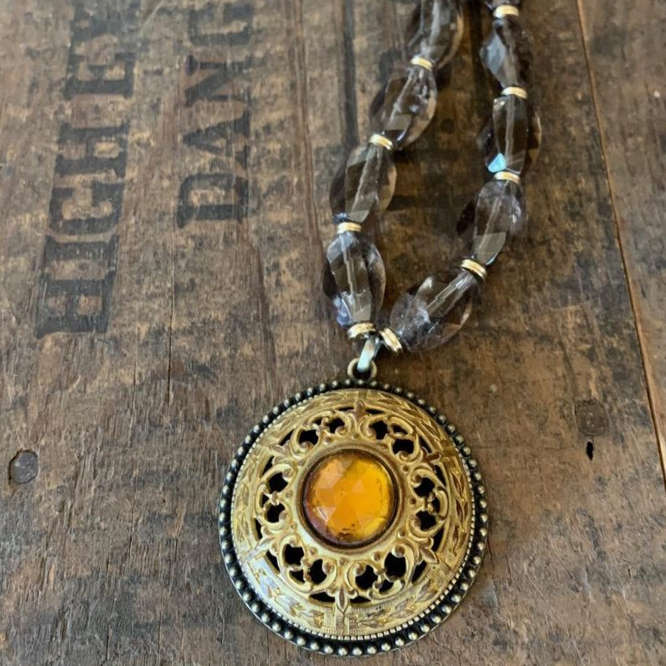 "An oversized pierced metal button has a topaz jewelled centre.  This piece hangs from an adjustable chain of smoky quartz and antique bronze.   Wear this piece at a 32"" length or adjust to 20""."
