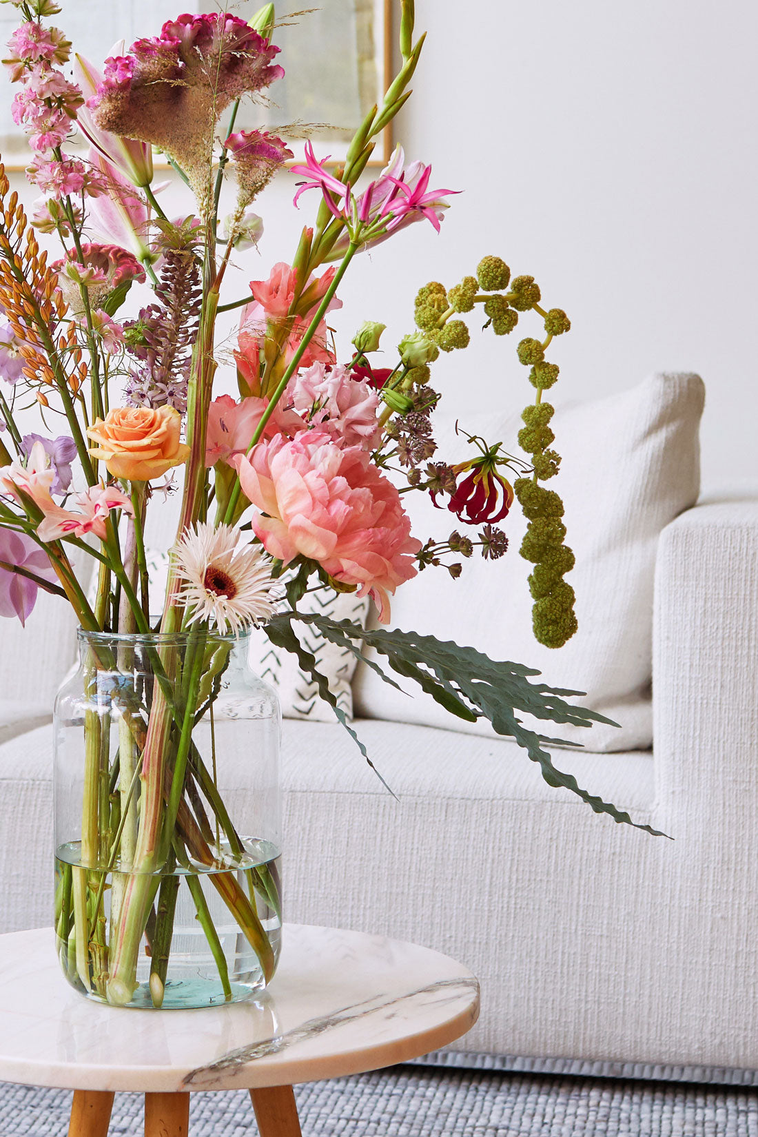 bloomon bouquet in original glass vase on a table with a bench
