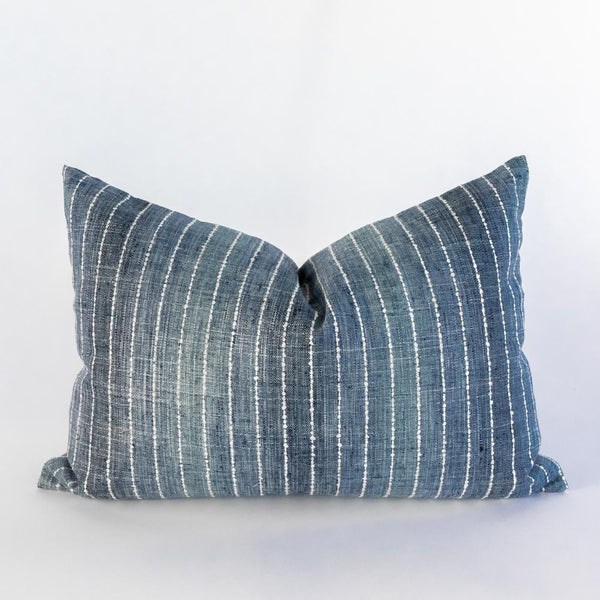 A striped lumbar pillow in tones of denim blue. The woven material has a textural slub, providing a hand-loomed look, with a soft white running-stitch stripe that has a nubbly organic quality. The mid blue shade has a gradient effect, creating the look of natural sun-worn vertical streaks that deliver a modern laid-back appeal.