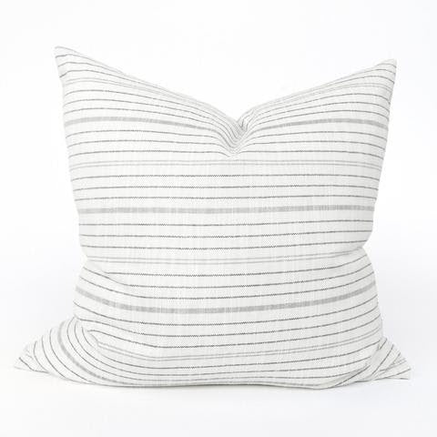 "The Terra Pillow color features black, cream and gray which mingle in this modern striped pillow that has a graphic yet understated look. Made of outdoor fabric, it will look equally chic on a sofa inside or outside on your patio. It's 22"" size makes it the perfect layering piece."