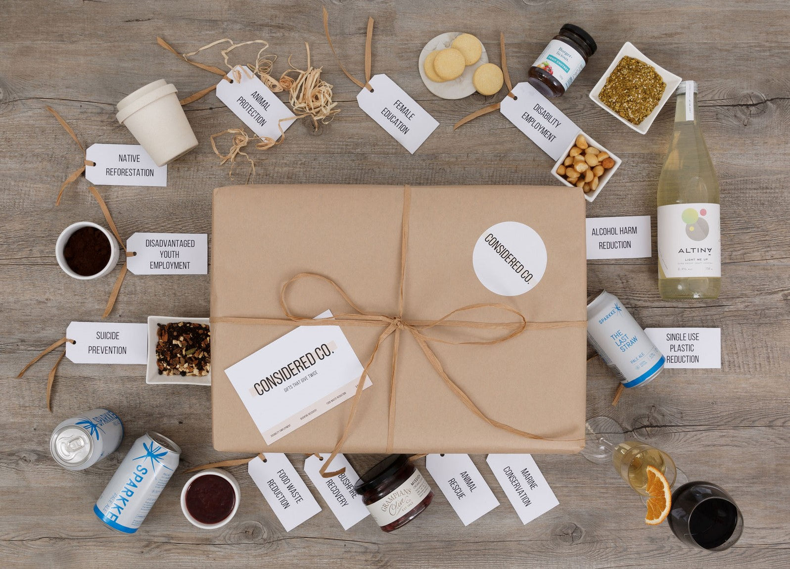 Wrapped gift with Considered Co. postcard surrounded by product samples and gift tags with each social cause they support. For example, tea that support suicide prevention, biscuits providing disability employment, wine that support marine conservation.
