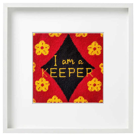 I Am A Keeper needlepoint kit, stitched, in a white frame