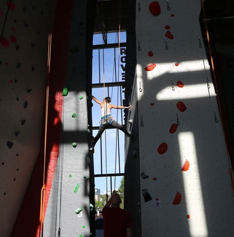 Woman straddles the chimney at an indoor rock climbing gym