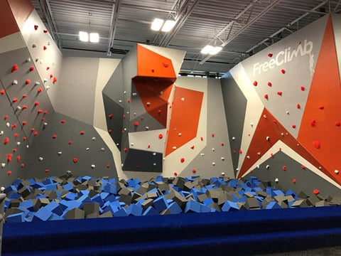 A foam pit sits below the bouldering wall in the FreeClimb area of the Asheville Sky Zone