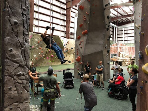 A female Adaptive climber ascends during a Paradox Sports triaining session at ProjectRock Climbing Gym