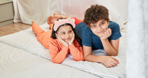 Young girl wearing a peach full sleeves night suit and a boy wearing a blue half sleeves pajama set lying on the floor