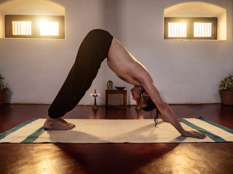 strong young man practicing yoga in old shala in Mysore, India. Downward facing dog on white organic cotton yoga rug