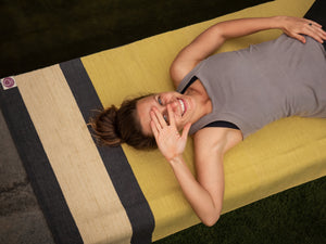 Girl lying in a savasana on the yellow cotton yoga mat is covering her face with hand, smiling,relaxing after yoga practice