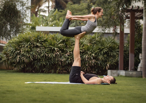 Yogic couple doing acroyoga in the garden. Using eco friendly yoga mat and performing Pigeon pose asana.